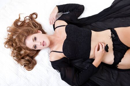 Alluring young woman lies on a bed while dressed in black lingerie. Horizontal shot. photo