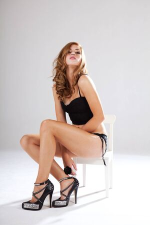 Alluring young woman in black lingerie sits in a white chair while looking into the camera. Vertical shot. Stock Photo - 7501316