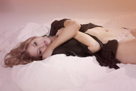 Sensual young woman lies in bed while wearing black sexy lingerie. Horizontal shot. photo