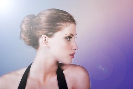 Side view of attractive young woman wearing a hair bun. Horizontal shot.