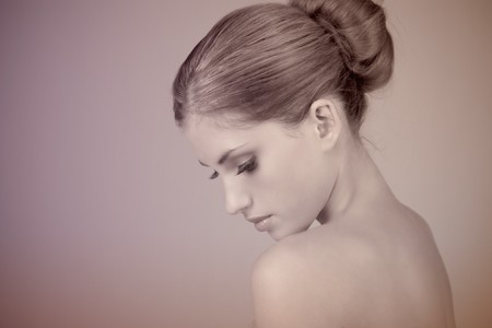 Side view of attractive young woman wearing a hair bun. She is pensively looking down. Horizontal shot. photo