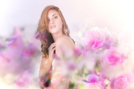 Beautiful young woman looking at the camera amidst flowers. Horizontal shot. photo