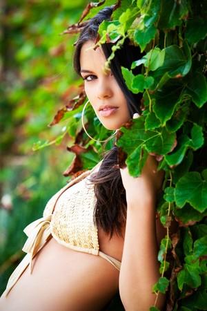 Beautiful young woman posing against an ivied wall in a yellow bikini.