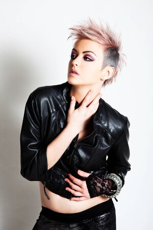 spiked hair: An attractive young female wearing punk fashion looks to the side with a blank expression. Vertical shot. Stock Photo