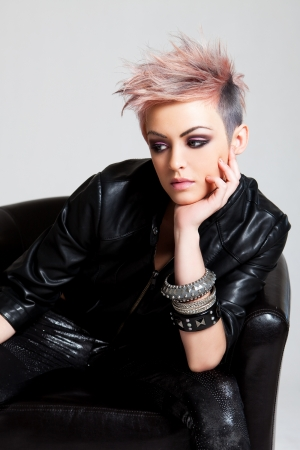 An attractive young woman with a serious expression is sitting in a chair and wearing punk attire. Vertical shot.