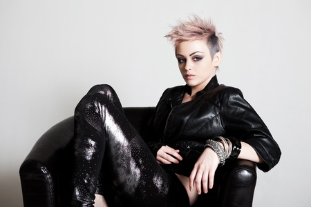 An attractive young female with a serious expression is sitting in a chair and wearing punk attire. Horizontal shot.