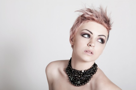 An attractive young topless female with a serious expression is wearing a necklace and looking down. Horizontal shot. Stock Photo