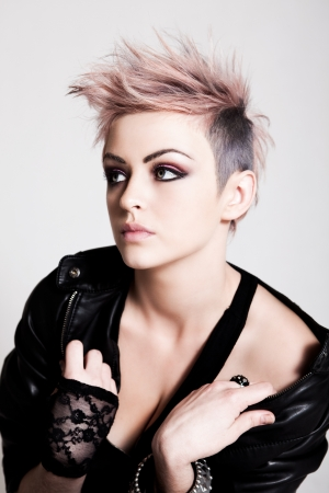 An attractive young woman with pink hair wearing a leather jacket and lace glove. Vertical shot. Stock Photo