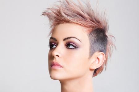 Head shot of a serious looking young woman sporting a pink punk haircut. Horizontal shot. Stock Photo
