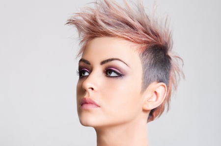 spiked hair: Head shot of a serious looking young woman sporting a pink punk haircut. Horizontal shot. Stock Photo