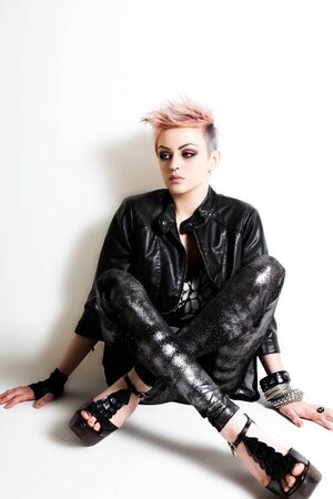 Young woman in punk fashion sits on the floor and looks pensively to the side. Vertical shot. Stock Photo - 9309735
