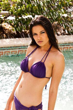 Beautiful young woman poses poolside while wearing a sexy bikini. Vertical shot. photo