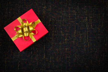 red gift box: Red gift box with gold ribbon bow on dark brown background