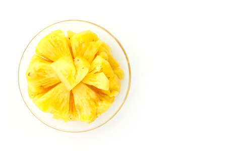 pineapple slice: Pineapple slice on a plate placed on a wooden table.