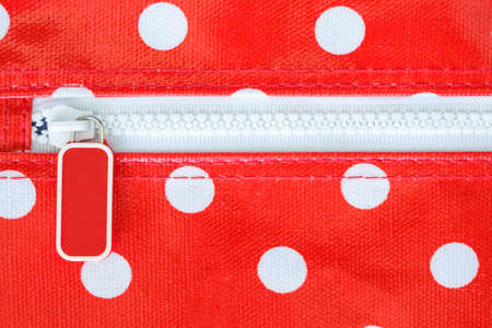 red bag: white zipper on white dots red bag Stock Photo