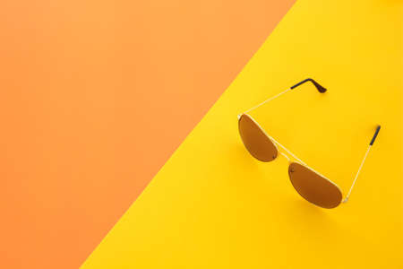vintage objects: sunglasses on orange and yellow background