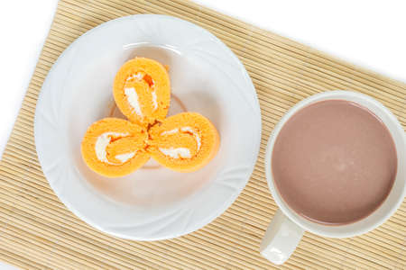 orange cake roll three piece on white plate and cup chocolate on wooden mat.
