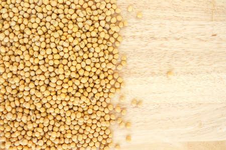 soja: soy bean heap on wooden background top view.