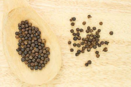 peppercorns: peppercorns in spoon heap on wooden table.