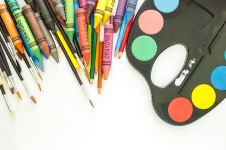 crayon pencil paint brush and paint tray multicolor set drawing on white background. Stock Photo