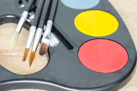 paint tray and paint brush on wooden background.
