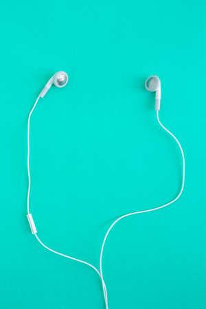 earbuds or earphones on green background