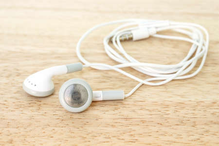 earbuds or earphones on wooden background Stock Photo