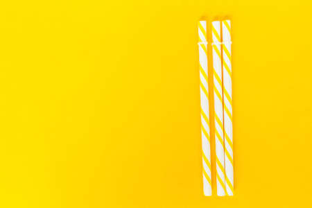 yellow striped straws on pink background