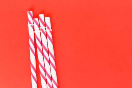 red striped straws on pink background