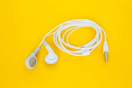 earbuds or earphones on yellow background