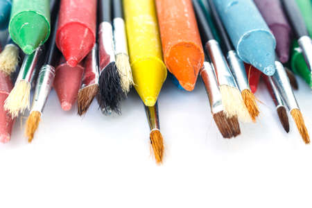 Crayon and paint brush on white background.