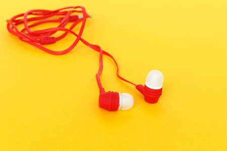 earbuds or earphones on yellow background