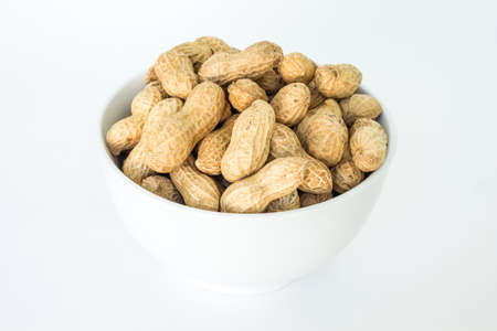peanut pile in white bowl top view on white background