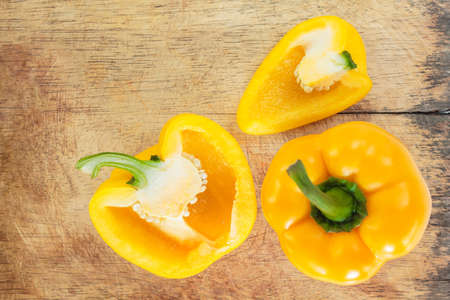 yellow bell pepper cut into pieces on wooden cutting board background, top view. Stok Fotoğraf