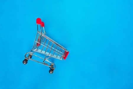 red shopping cart top view on blue background.