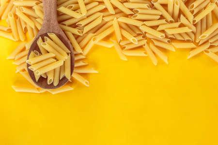 dry pasta penne Italian food yellow background. Stok Fotoğraf