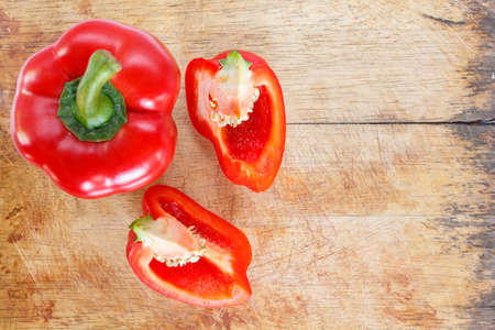 red bell pepper cut into pieces on wooden cutting board background.