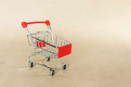 red shopping cart on brown background. Stok Fotoğraf