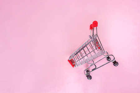 red shopping cart top view on pink background.