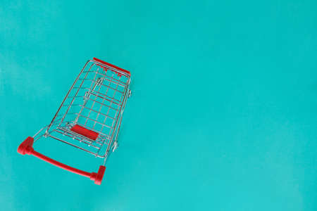 red shopping cart top view on green background. Stok Fotoğraf