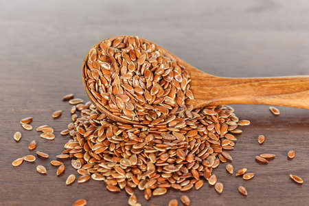 Brown flax seed in spoon on wooden background. Archivio Fotografico - 128962677