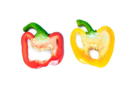 red and yellow bell pepper cut half into pieces on white background, top view. Archivio Fotografico - 128962851