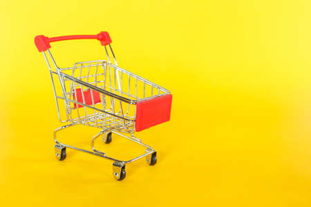 red shopping cart on yellow background. Archivio Fotografico - 128962997