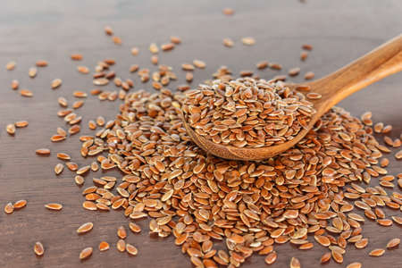 Brown flax seed in spoon on wooden background. Archivio Fotografico - 128963127
