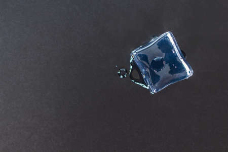 Ice cube on black background. Archivio Fotografico - 128963680