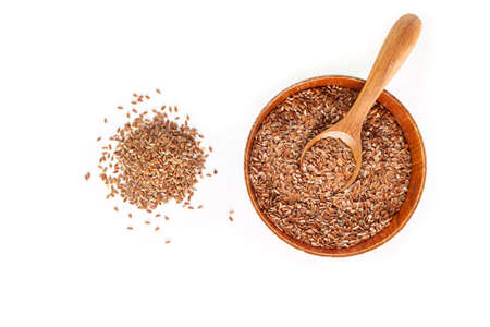 Brown flax seed in bowl and spoon on white background. Archivio Fotografico - 128963755