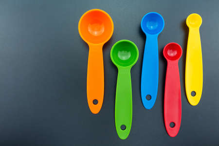 a set of measuring spoon of plastic on black background.