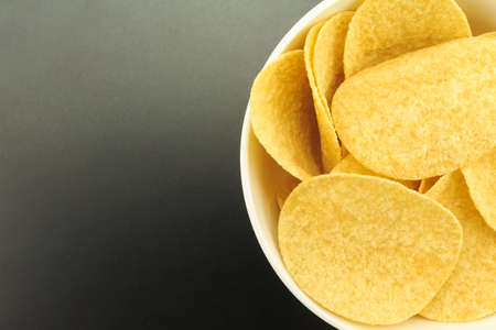 potato chips on bowl on black background. Stock Photo - 145473916