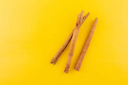 cinnamon on yellow background. Reklamní fotografie