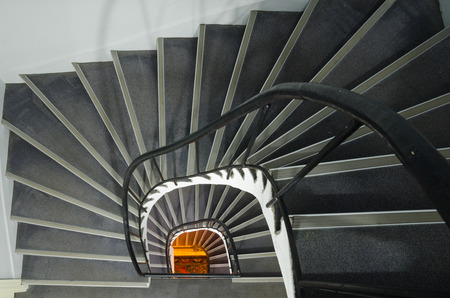 Spiral staircase with warm orange light at the end photo